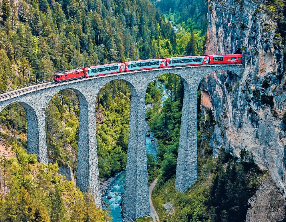 bernina express passing through tunnel and over bridge